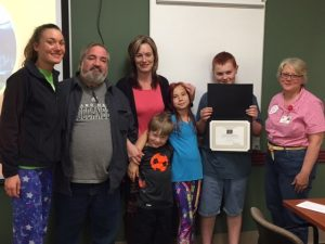 Kent Zoet accepts his award with his family and Terri Sakal-Brockway, Allegan Healthcare Group.