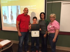 Skyler Hilton accepts his award with his parents and Terri Sakal-Brockway, Allegan Healthcare Group.